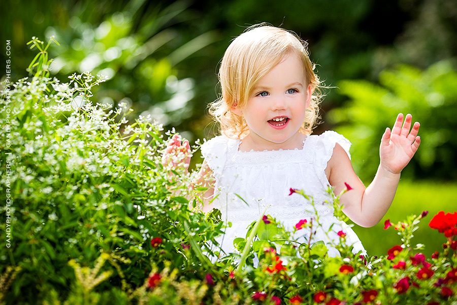 child-by-red-flowers